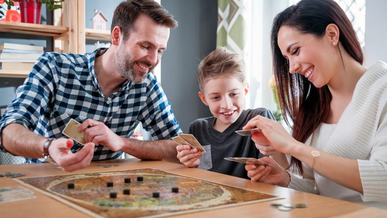 Rodzice grają z dzieckiem w grę planszową