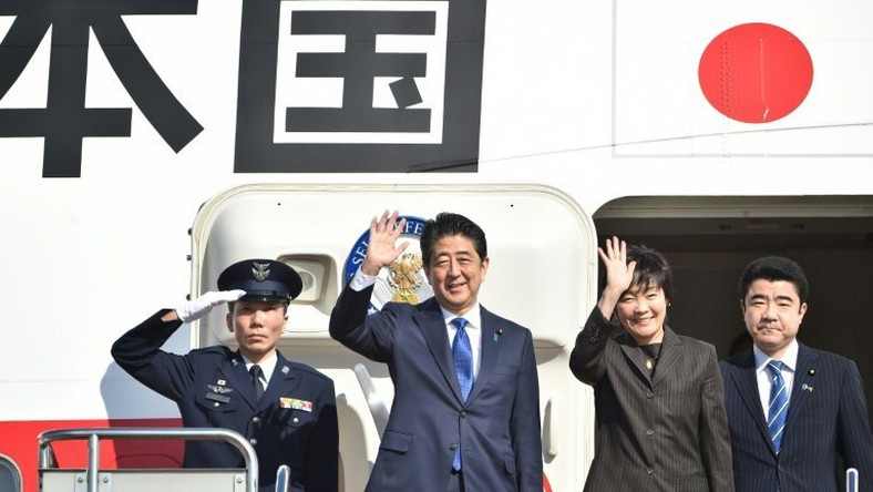 Japan's Prime Minister Shinzo Abe (2nd L) and his wife Akie wave to well-wishers prior to boarding a government plane at Tokyo's Haneda on November 17, 2016