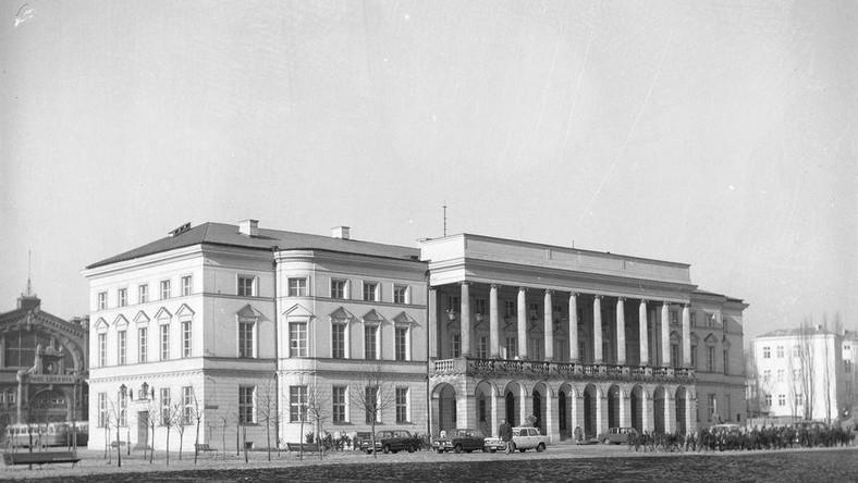 Obrócony Pałac - widok od pl. Żelaznej Bramy, rok 1976 Po co w ogóle przesuwać i tak z trudem odbudowany po wojnie XVIII-wieczny Pałac Lubomirskich? Powód był w zasadzie prozaiczny. Chodziło o takie ustawienie gmachu, by po pierwsze, zamykał kompozycję Osi Saskiej, a po drugie - nie przeszkadzał w planach budowy nowego osiedla mieszkaniowego. źródło: Narodowe Archiwum Cyfrowe