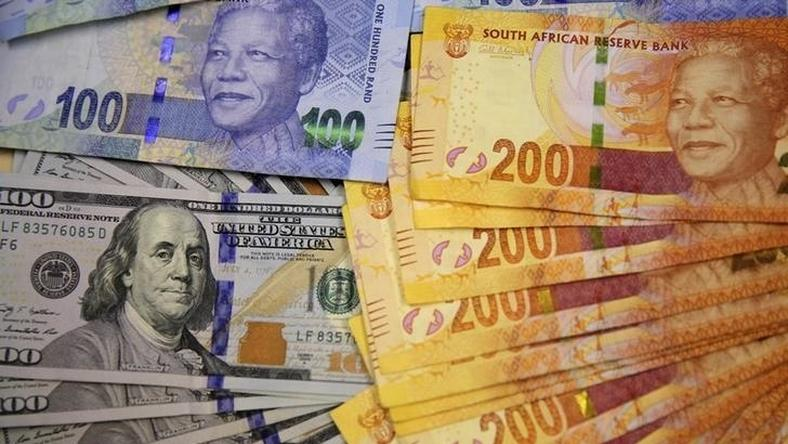 South African bank notes featuring images of former South African President Nelson Mandela (R) are displayed next to the American dollar notes in this photo illustration in Johannesburg August 13 2014.   REUTERS/Siphiwe Sibeko