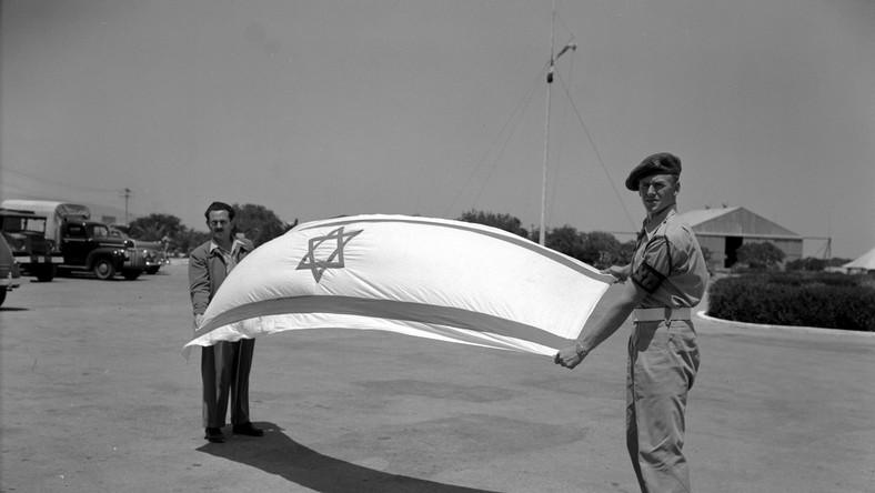 14 maja 1948 roku proklamowano państwo Izrael. Flaga państwowa nawiązuje do tradycyjnej żydowskiej chusty modlitewnej Talit. Pośrodku flagi jest umieszczona Gwiazda Dawida, która od setek lat pozostawała symbolem żydowskiej tożsamości narodowej. Oficjalnym herbem państwowym jest złoty świecznik menora