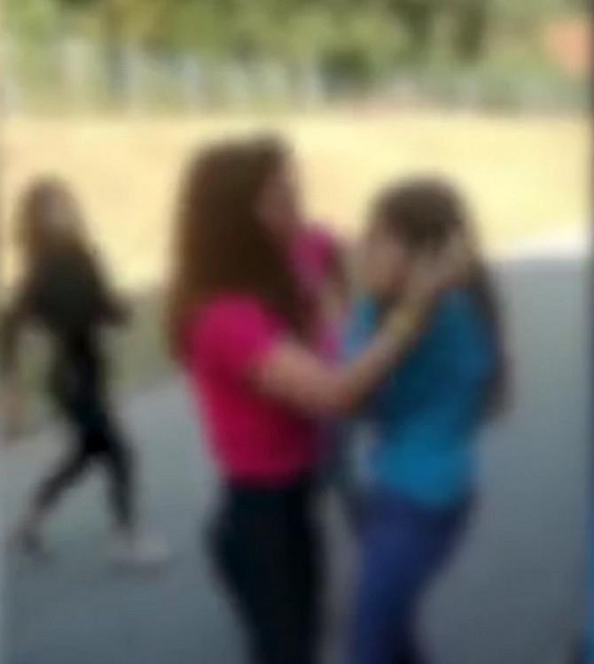 Devojčicu šamaraju dve devojčice, deca posmatraju sa strane i snimaju mobilnim telefonima