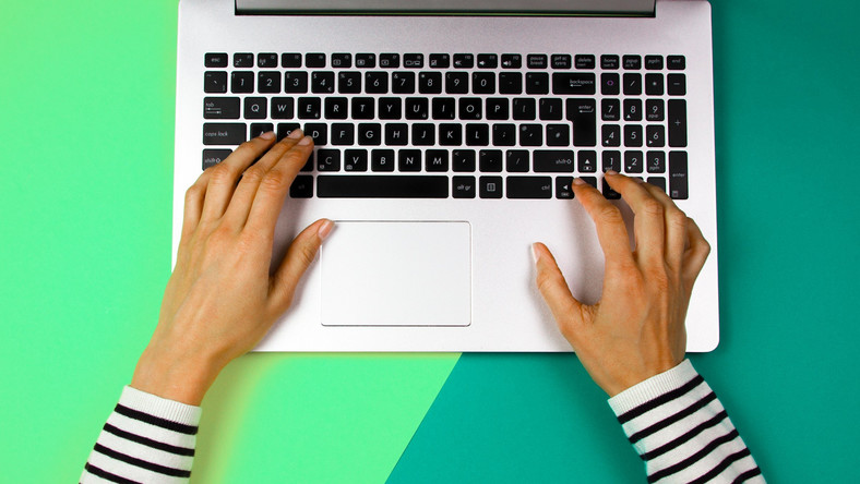 Woman using Apple Mac laptop over colorful background