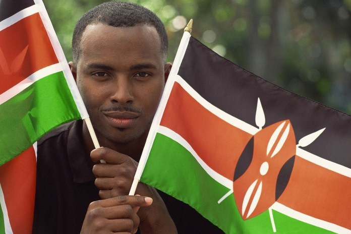 A Kenyan holding two flags.