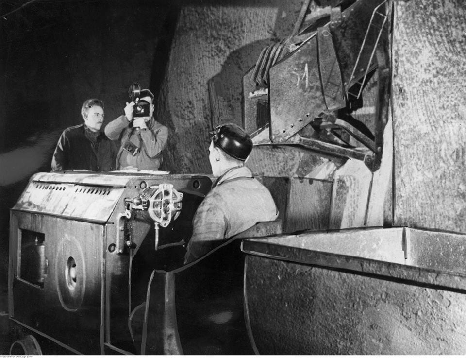 Filmowanie kopalni soli w Wieliczce. Kamerzysta filmuje górnika prowadzącego kolejkę z wagonikami, rok 1940
