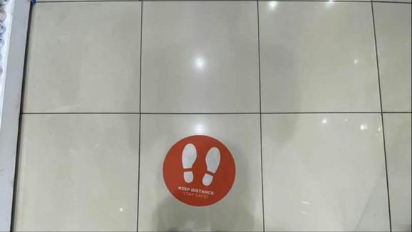 U marketima stoje nalepnice na podu koje upućuju na potrebnu distancu između potrošača