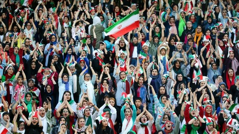 Wearing sporty hats and the national flag, Iranian women cheer for their team at a game they will never forget.