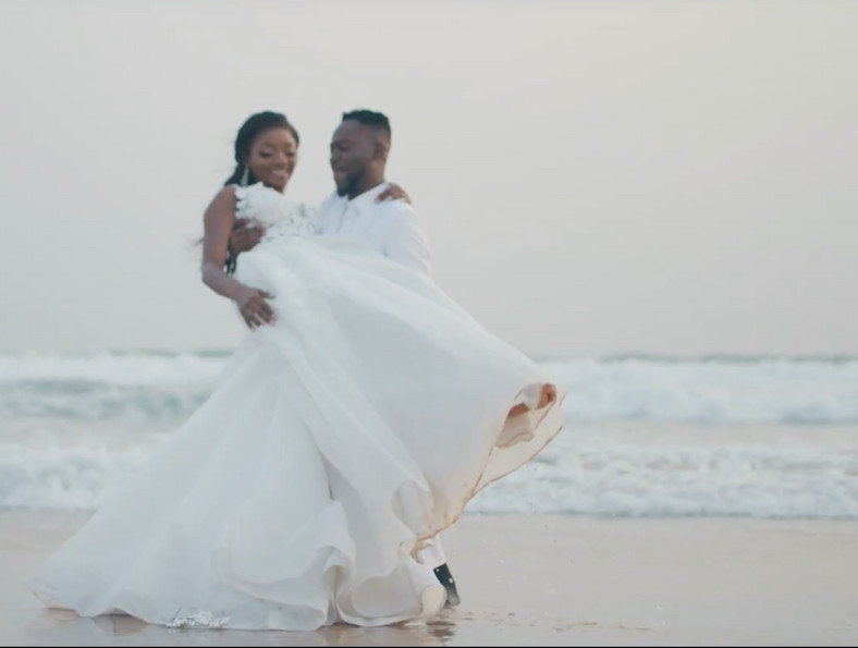 The wedding ceremony took place at the Ilashe beach in Lagos. Unlike the traditional wedding which had a larger turnout, the white wedding was attended by a reportedly selected 300 guests. [Credit: Youtube/ Vevo/ Adekunle Gold]