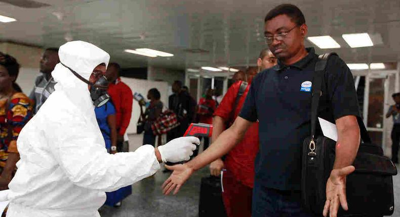 A health official uses a thermometer on a passenger at the international airport in Lagos, Nigeria