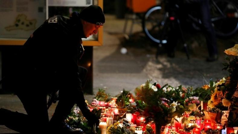 Mourners placed flowers and candles at the site where a truck rampaged through a Berlin Christmas market killing 12, a flags flew at half-mast