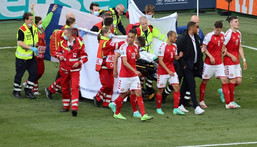 Denmark's players gather as medics treat midfielder Christian Eriksen during the Euro 2020 match against Finland Creator: WOLFGANG RATTAY