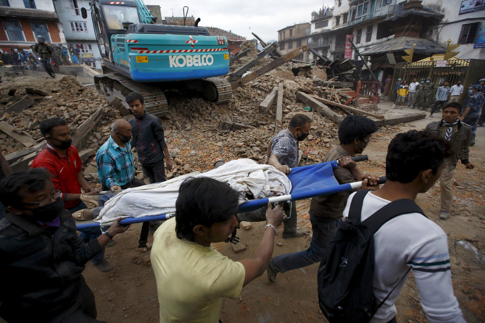 Rescue workers carry the body of a victim on a stretcher, after a 7.9 magnitude earthquake hit, in Kathmandu, Nepal