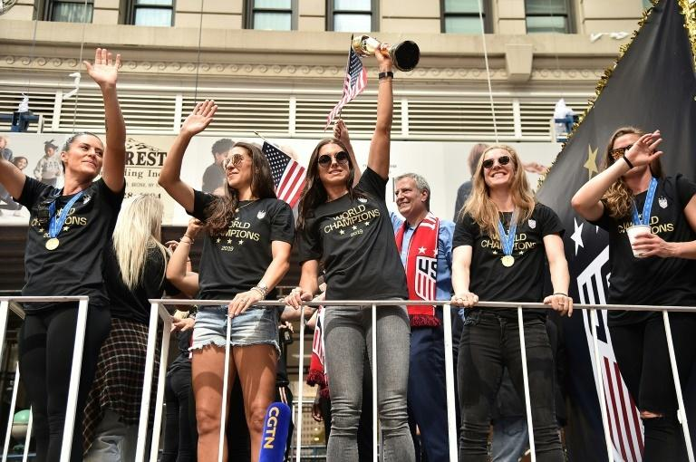 Alex Morgan waves the World Cup trophy as the US women's soccer team is feted with a ticker tape parade in New York