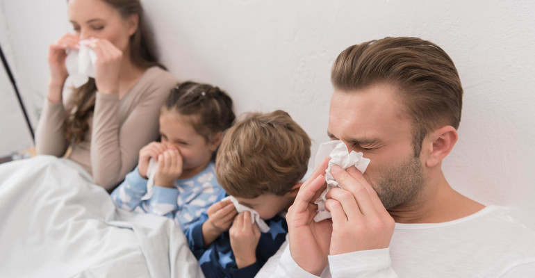 family blowing noses in napkins