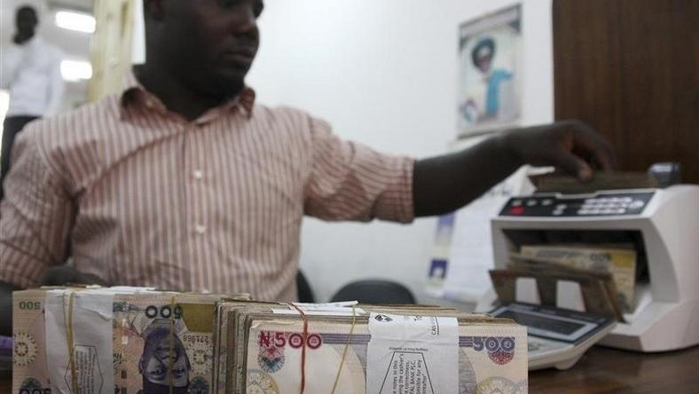 A money dealer counts the Nigerian naira on a machine in his office in the commercial capital of Lagos, January 13, 2009.   REUTERS/Akintunde Akinleye