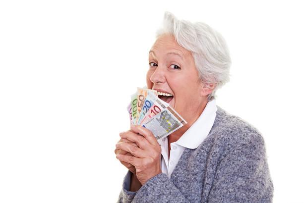 Seniorka z plikiem banknotów w dłoni. Fot. Shutterstock