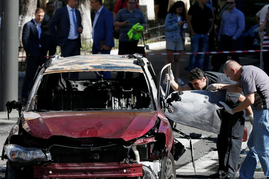 Investigators inspect a damaged car at site where journalist Pavel Sheremet was killed by a car bomb