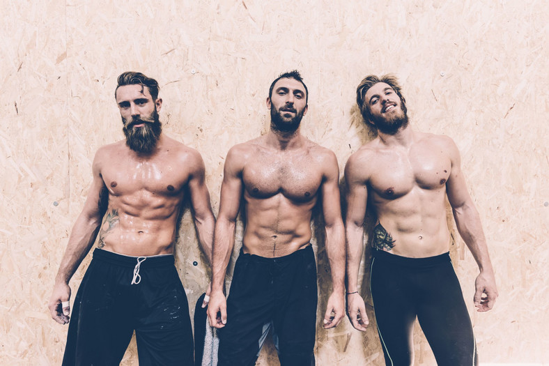 Portrait of three macho male cross trainers in gym