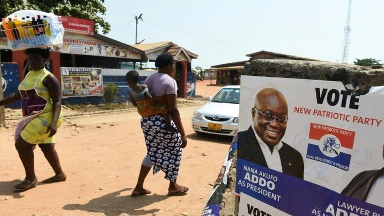 People walk past a campaign poster of presidential candidate of the opposition New Patriotic Party Nana Akufo-Addo in Accra, on December 3, 2016 ahead of the December 7 election