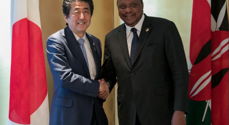 Japan's Prime Minister Shinzo Abe shakes hands with Kenyan President Uhuru Kenyatta.