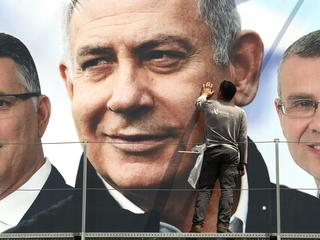 A labourer works on hanging up a Likud election campaign banner depicting Israeli Prime Minister Ben