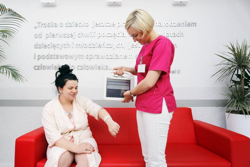 Julia Słomian, położna w szpitalu skanuje opaskę pacjentki Sandry Janek