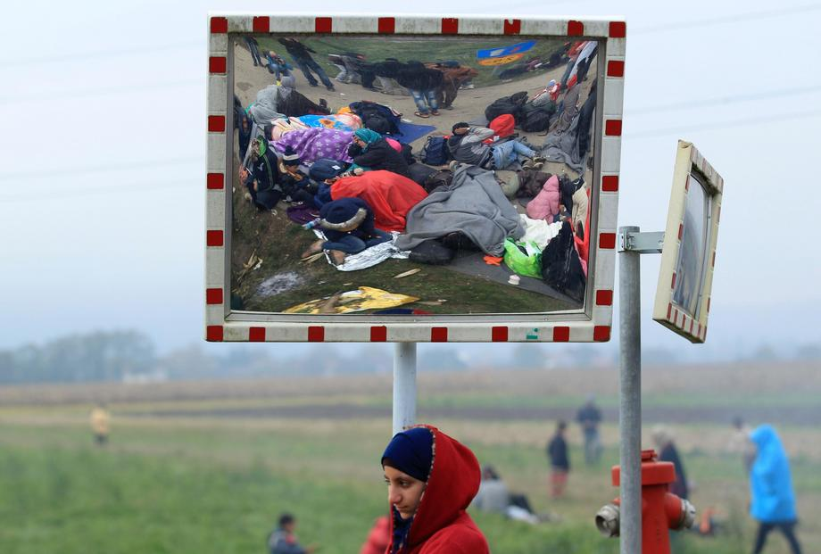 A girl looks on as resting migrants are seen in a street mirror after crossing the border from Croat