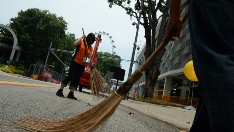Singaporean volunteers sweep a public area inside the circuit of the Formula One Grand Prix in 2014: the future of the event is uncertain