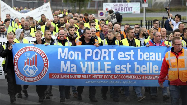 Harbor workers, storekeepers and residents march to participate in a human chain protest demonstration against the migrant situation in Calais