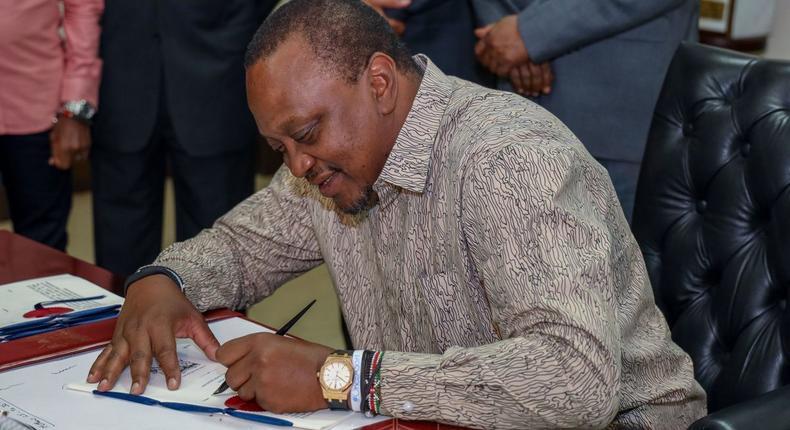 President Uhuru Kenyatta signing a document in his office