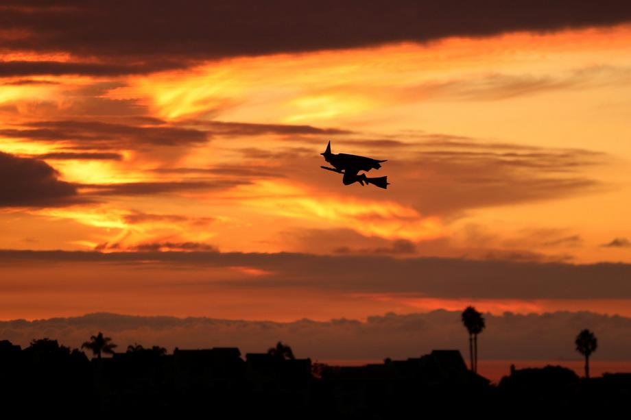 A remote controlled witch on a broom flies over a Southern California neighborhood after sunset on H