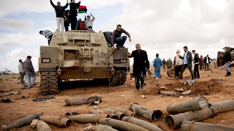 Rebelianci na spalonym czołgu, należącym do sił Muammara Kadafiego, zniszczonym podczas francuskiego nalotu 25 km od Bengazi