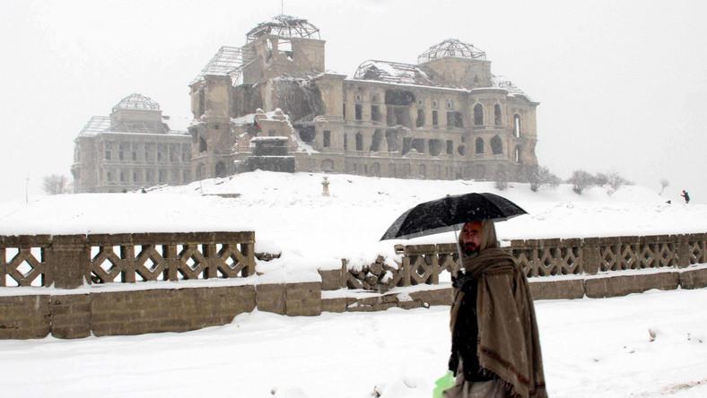 Okryty kocem mężczyzna przechadza się w okolicach zniszczonego pałacu Darul Aman