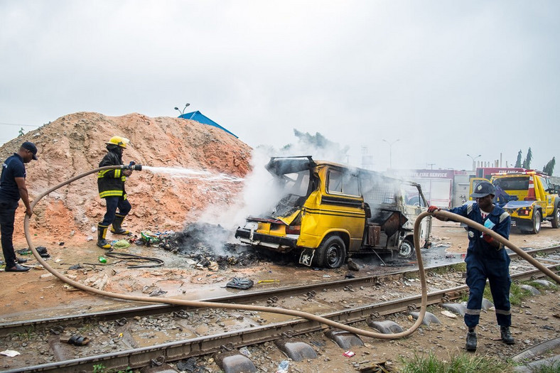 Train crashes into 'danfo' bus in Lagos. Emergency workers are seen trying to clear the scene.