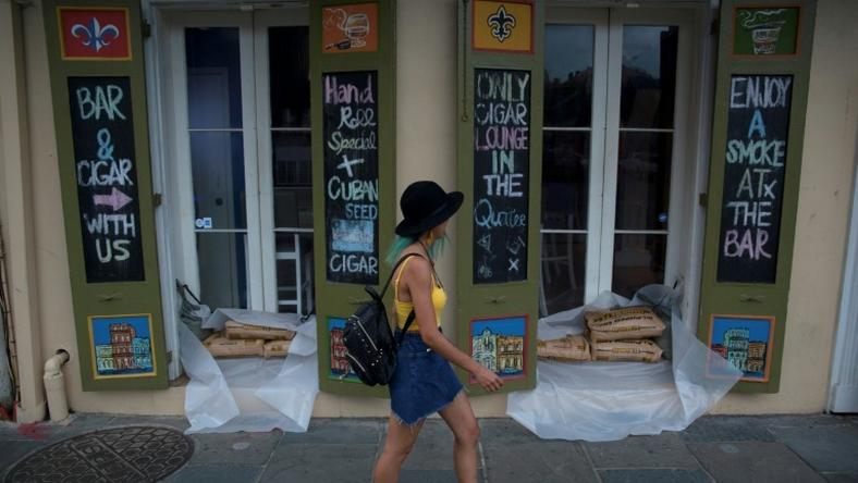 A woman walks past a cigar lounge and bar protected by sand bags in the French Quarter of New Orleans, in preparation for tropical storm Barry