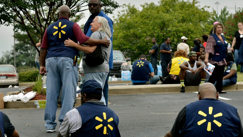 FILE - In this July 30, 2019, file photo Walmart employees gather in a nearby parking lot after a shooting at the store in Southaven, Miss. The discounter has dealt with thousands of violent crimes at its stores across the country, including one that took place less than a week ago at a store in Mississippi where a disgruntled worker killed two co -workers and wounded a police officer. (AP Photo/Brandon Dill, File)