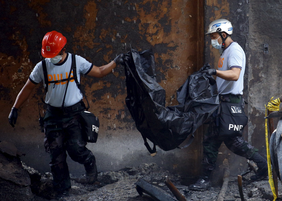 Police carry a body bag containing a charred remains of a worker inside a gutted slipper factory in Valenzuela