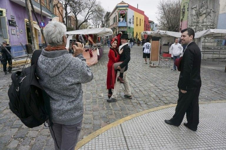 A tourist takes pictures of a couple dancing tango at the traditional street museum Caminito in La Boca neighborhood in Buenos Aires