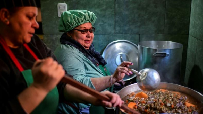 Women serve food at a soup kitchen which feeds at least 200 people hit hard by the economic crisis