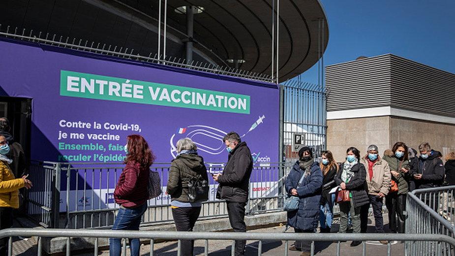Ludzie stojący w kolejce przed paryskim Stade de France po przekształceniu go w centrum szczepień przeciw COVID-19