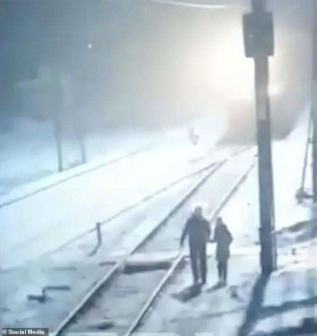 Marina sa ocem pored pruge dok im voz prilazi s leđa