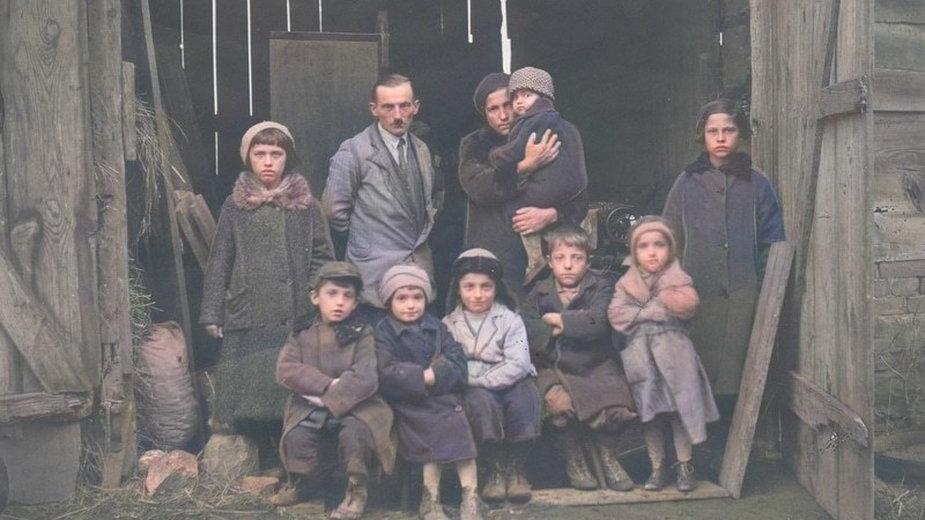 Członkowie rodziny bezrobotnego przed stodołą służącą za mieszkanie. 1935 rok. Źródło: Narodowe Archiwum Cyfrowe.
