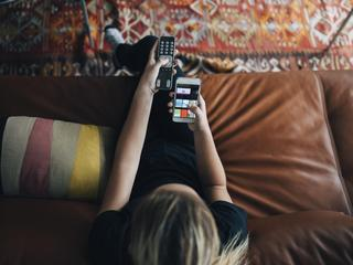 High angle view of teenage girl using phone app and remote control while sitting on sofa watching TV