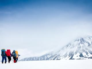 Group with gear and backpacks crossing icy field to mountain