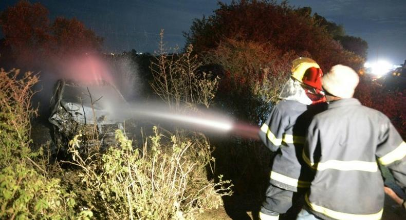 Firefighters put out a fire on a burning car which was involved in an accident with an oil tanker near the town of Naivasha, Kenya, on December 11, 2016