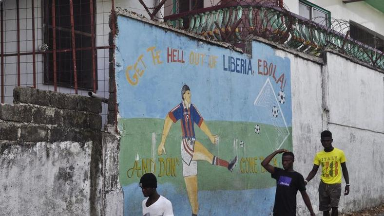 "Men walk by a mural that reads ""Get the hell of Liberia, Ebola! And don't come back"" in Monrovia, Liberia, April 1, 2016. REUTERS/James Giahyue"