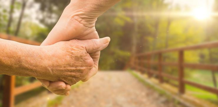 penzioneri starije osobe se drže za ruke
