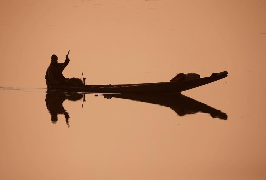 A fisherman rows his boat through the waters of the Dal Lake on a cold morning in Srinagar