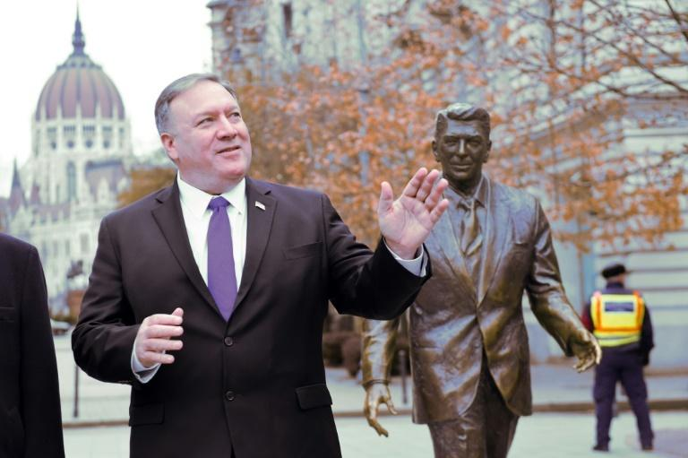 US Secretary of State Mike Pompeo poses next to a picture of former president Ronald Reagan in Budapest