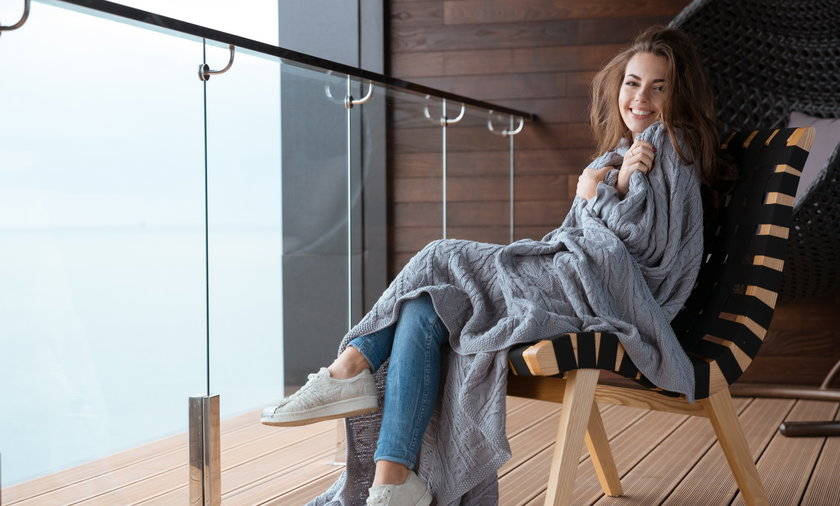 Funny girl with tousled hair sitting wrapped in knitted coverlet